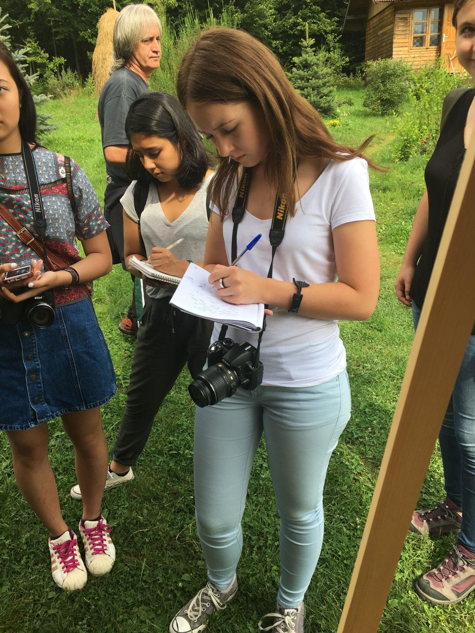 Teenage volunteer takes note during an interview on her Journalism Project in Romania